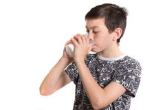 Young teenage boy drinking milk. Young teenage boy drinking a glass of milk royalty free stock photography