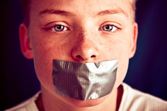Young Teenage Boy with Duct Tape Covering Mouth. Extreme Close Up of Young Pre Teenage Boy with Serious Expression Staring at Camera with Piece of Duct Tape stock photos