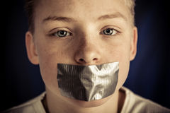 Young Teenage Boy with Duct Tape Covering Mouth. Extreme Close Up of Young Pre Teenage Boy with Serious Expression Staring at Camera with Piece of Duct Tape royalty free stock image