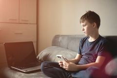 Boy with smarphone. Young teenage boy in his room at home holding smatphone sitting on the bed by computer Royalty Free Stock Photos