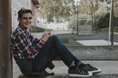 Young teenage boy holding mobile phone. Young smiling teenage boy in red and white check shirt and blue jeans sitting on the floor outside holding his mobile Royalty Free Stock Image