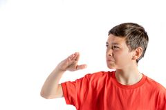 Young teenage boy. Isolated on a white background wafting a smell away Royalty Free Stock Images