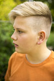 Young teenage boy with a modern hairstyle. Close up profile portrait of the face of an attractive young teenage boy with a modern blond hairstyle Royalty Free Stock Images