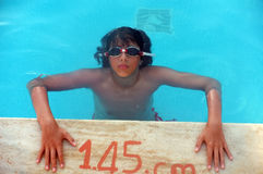 Young teenage boy on poolside. Inside water and head and arms out of water Royalty Free Stock Photos