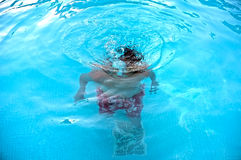Young teenage boy underwater in swimming pool Stock Photo