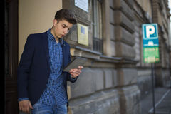 Young teenage boy uses the tablet in the parking lot Stock Photography