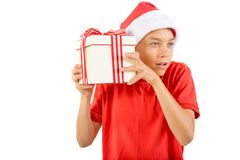 Young teenage boy wearing a Santa Christmas hat with a gift Stock Photos