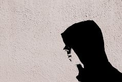 Young teenage bully boy in black hoodie with graffiti stencil effect on white wall Stock Photography