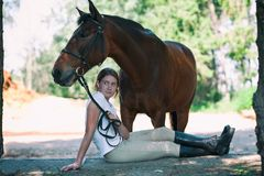 Young teenage cheerful girl equestrian hugging her favorite chestnut horse stock images