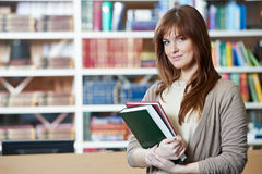 Female student girl with books in library Royalty Free Stock Photography