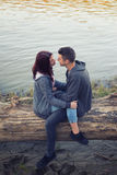 Young teenage couple sitting on fallen tree trunk on river shore royalty free stock image