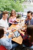 Young cheerful friends chatting at the cafe on the outdoors background. Friendship concept. Royalty Free Stock Images