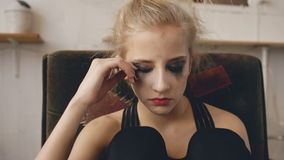 Young teenage girl actress with smudged makeup smiles after stop crying becuase of loss film casting