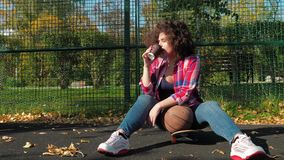 A young teenage girl sits on a skateboard on the playground, drinks coffee from a paper cup and holds a basketball ball. A young teenage girl with an african stock footage