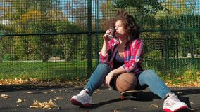 A young teenage girl sits on a skateboard on the playground, drinks coffee from a paper cup and holds a basketball ball. A young teenage girl with an african stock video