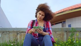A young teenage girl with an african hairstyle is sitting in a park on a lawn or city street and counting money Euro. Banknotes. The concept of making money and stock video