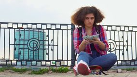 A young teenage girl with an African hairstyle is sitting on a skateboard on a city street and counting money euro. Banknotes. The concept of making money and stock video footage