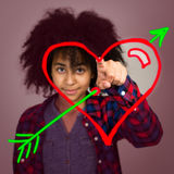 Young Teenage Girl With Afro Hair Drawing A Love Heart. A mixed race teenage girl with afro hairstyle drawing a love heart with arrow in the air Royalty Free Stock Photography