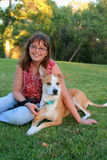 Young teenage girl and Australian mix dog. A pretty 13-year-old young teenager and her dog are sitting on the lawn at a park. The girl is wearing stylish glasses Stock Photos