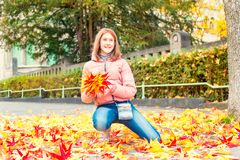 Young teenage girl in autumn park with fall leaves bouquet Stock Photography