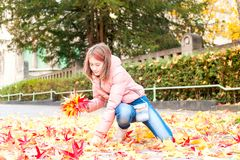 Young teenage girl  in autumn park picking leaves. Fall season. Royalty Free Stock Photo