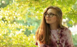 Girl Day Dreams. Young teenage girl with black glasses day dreaming oute with trees in the background royalty free stock photography