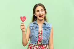 Young teenage girl with blondie long hair, wink at camera, tongue out, holds lolipop, having funny look. Royalty Free Stock Photography