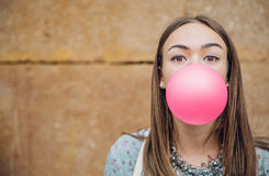 Young teenage girl blowing pink bubble gum. Closeup of beautiful young brunette teenage girl blowing pink bubble gum over a stone wall background royalty free stock photo