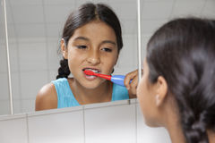 Young teenage girl brushing her teeth Royalty Free Stock Image