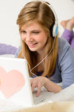 Young teenage girl chatting on laptop Stock Photo