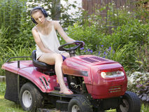 Young teenage girl cutting the lawn Royalty Free Stock Photo