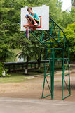 Young teenage girl fixing a basketball net Royalty Free Stock Photography