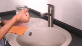 Young teenage girl getting a glass of water stock footage