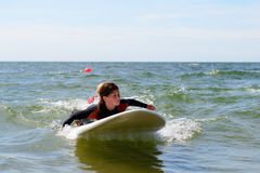 Young teenage girl getting surf lessons on vacation. stock photos