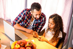 Young teenage girl with her father. A young brown teenage girl siting at the kitchen table with her father and using a smartphone r Stock Photos