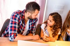 Young teenage girl with her father. A young brown teenage girl siting at the kitchen table with her father and using a smartphone r Stock Images