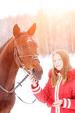 Young teenage girl with her horse in winter park Royalty Free Stock Images