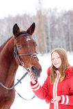 Young teenage girl with her horse in winter park Stock Photography