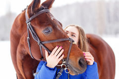 Young teenage girl with her horse in winter park. Young teenage girl spending time with her friend bay horse in winter park. Friendship concept image stock photography