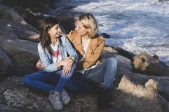 Young teenage girl with her mother in affectionate gesture by the sea. Family vacations on the coast stock images