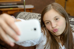 Young teenage girl on home sofa couch taking selfie Stock Photo