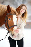 Young teenage girl with horse in winter park Royalty Free Stock Photos