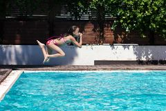 Young girl jumping into pool Stock Images