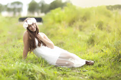 A young teenage girl laying in a field with a white dress. Stock Image