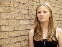Young teenage girl looking sad or depressed. In front of a brick wall background Royalty Free Stock Image