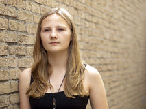 Young teenage girl looking sad or depressed. In front of a brick wall background Stock Photo