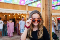 A young teenage girl looks over her sunglasses and smiles at an open-air market. royalty free stock images