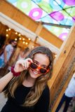A young teenage girl looks over her sunglasses and smiles at an open-air market. stock photo