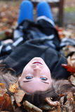 Young teenage girl lying upside down on a bed of leaves. In Autumn Stock Image
