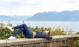 Girl. Teenage. Lying. View. Outdoor. Young teenage girl lying on the wall with beautiful Geneva lake on the background stock photo